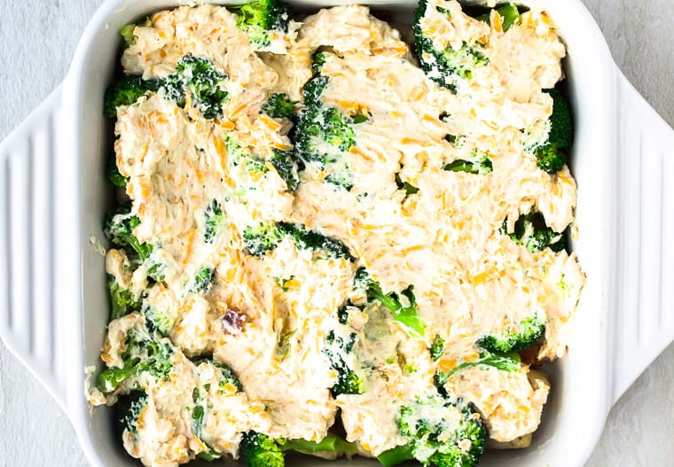 Cream Cheese mixture spread over top of chicken, broccoli, and bacon in a white casserole dish