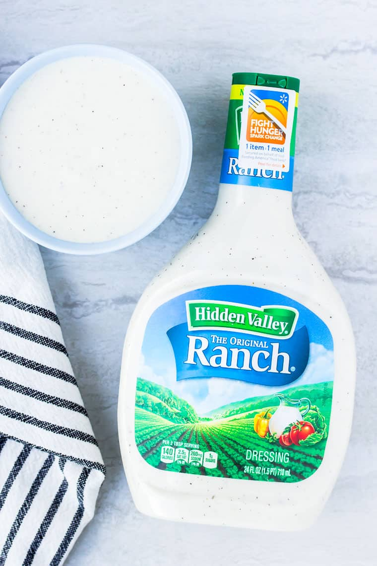 Hidden Valley Ranch bottle on a white backdrop with a blue bowl filled with the dressing and a black and white dish towel