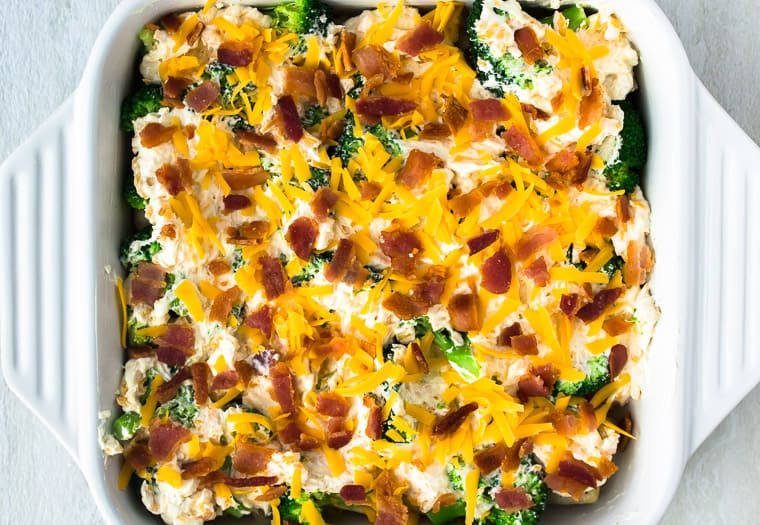 Ranch Bacon Chicken Casserole topped with extra cheese and bacon crumbles in a white casserole dish