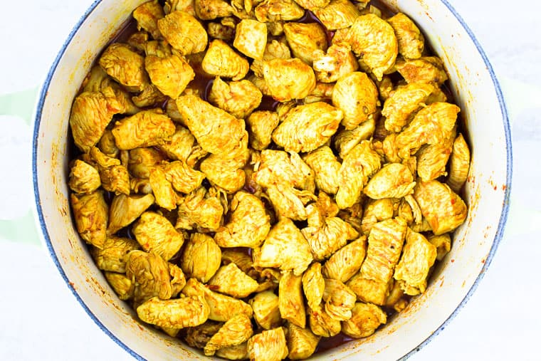 Curry chicken pieces in a dutch oven over a white background