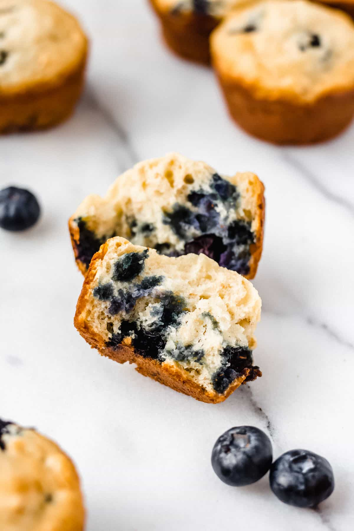 Blueberry muffin broken in half with other muffins and blueberries around it