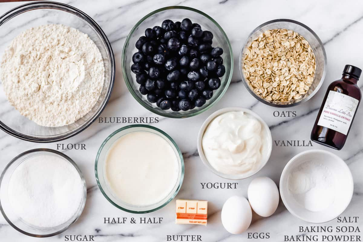 Ingredients needed to make blueberry oat muffins on a marble backdrop with labels
