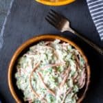 2 wooden bowls of brussels sprouts coleslaw on a piece of slaw over a gray background with a fork and blue and white striped towel