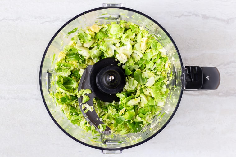 Brussels sprouts shredded in a food processor bowl over a white background