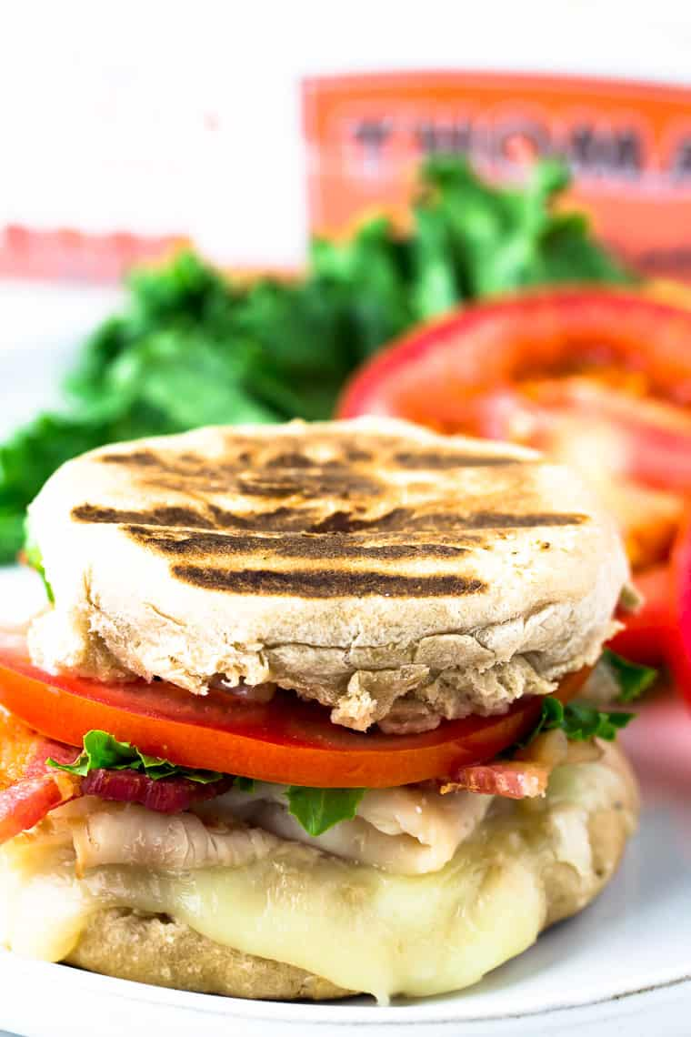 Grilled Turkey BLT Sandwich with lettuce, tomato and Thomas English Muffins in background