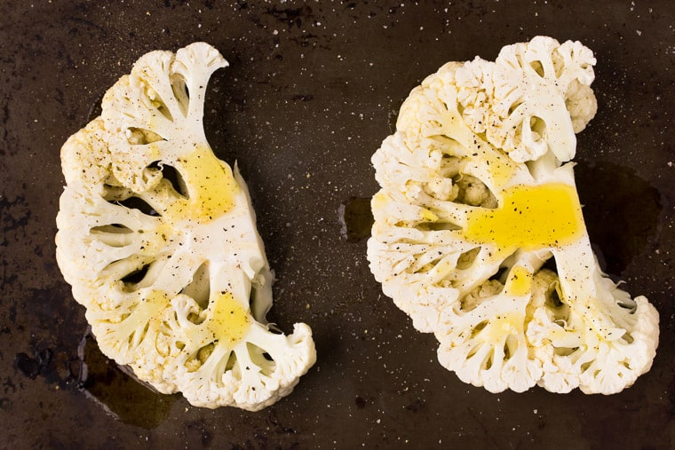 2 cauliflower steaks on a sheet pan with olive oil, salt and pepper on them
