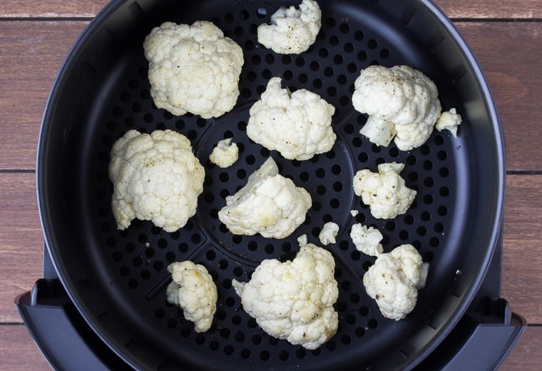 Raw cauliflower florets in the bottom of an air fryer