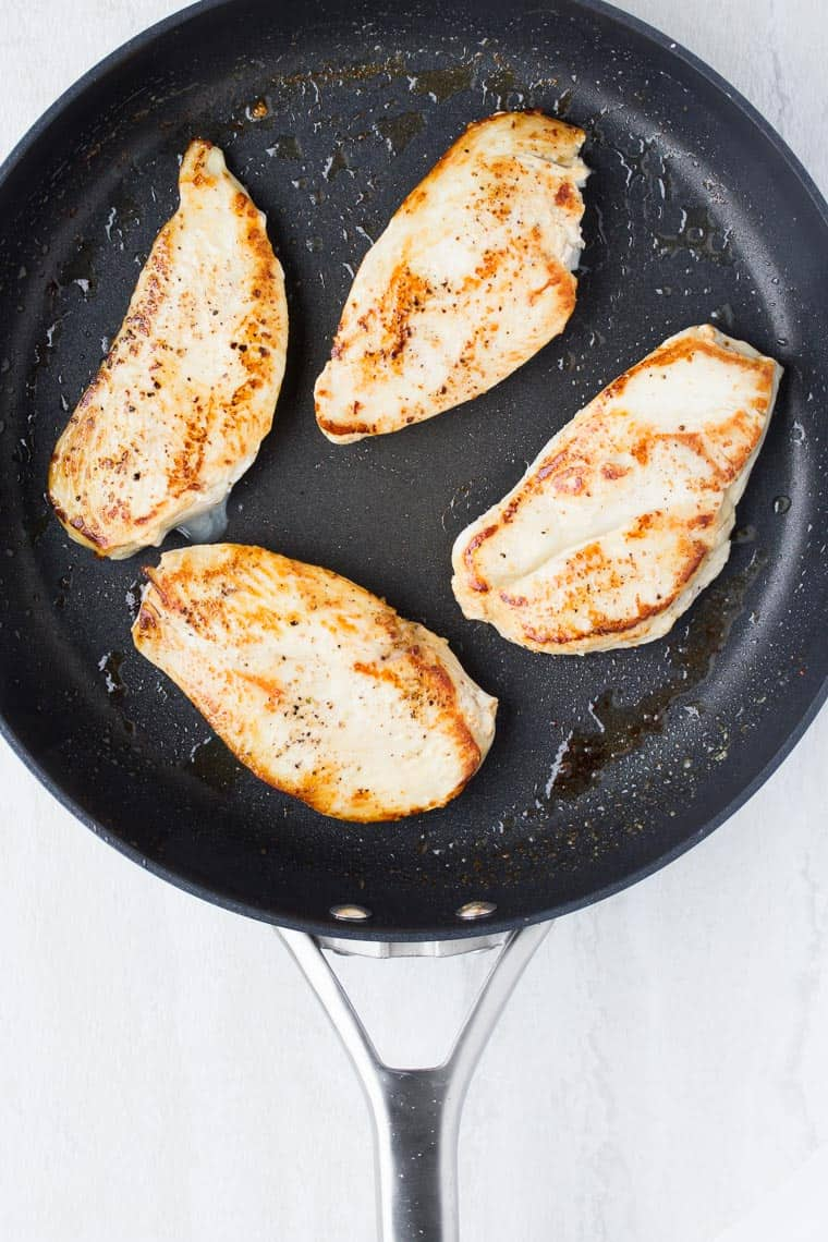 4 cooked chicken breasts in a black skillet over a white background
