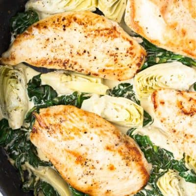 Spinach Artichoke Chicken close up in a black skillet
