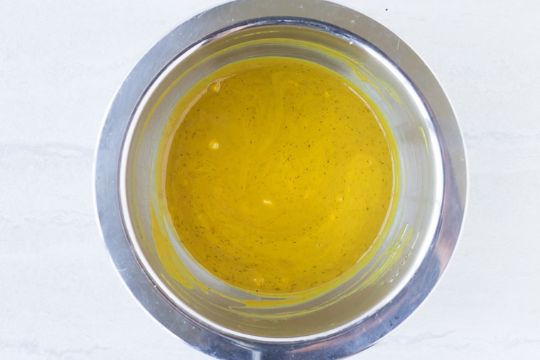 Mustard sauce in a silver bowl on a white background