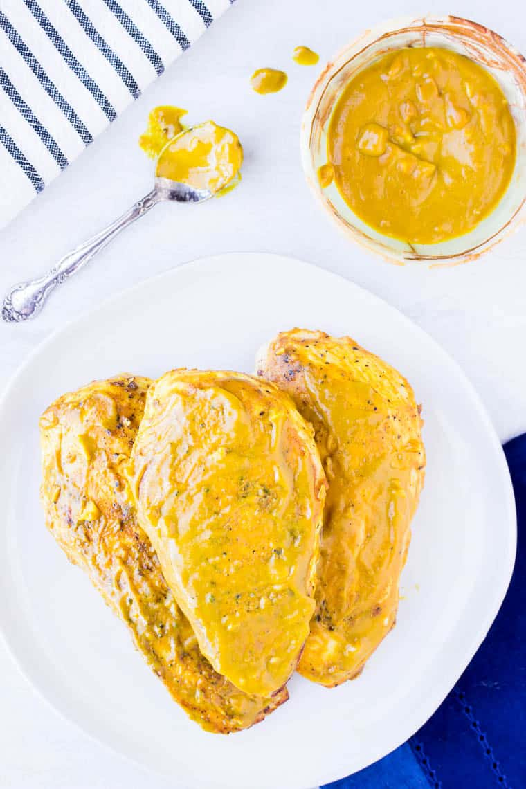 3 Baked Mustard Chicken Breasts on a white plate with a bowl of mustard sauce, a spoon, a blue napkin, and a black and white napkin in the background