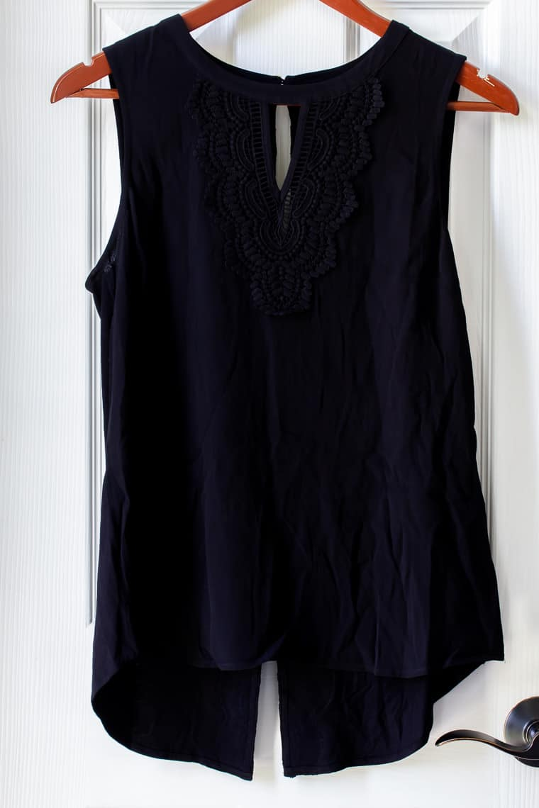 Black Pale Sky Quin Keyhole Crochet Top on a hanger over a white door