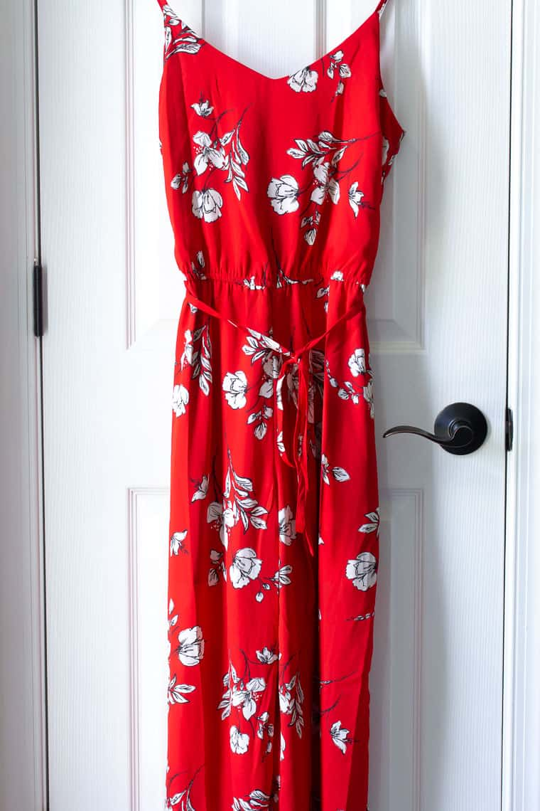 Red Skies are Blue Danica Jumpsuit with white flowers hanging over a white door