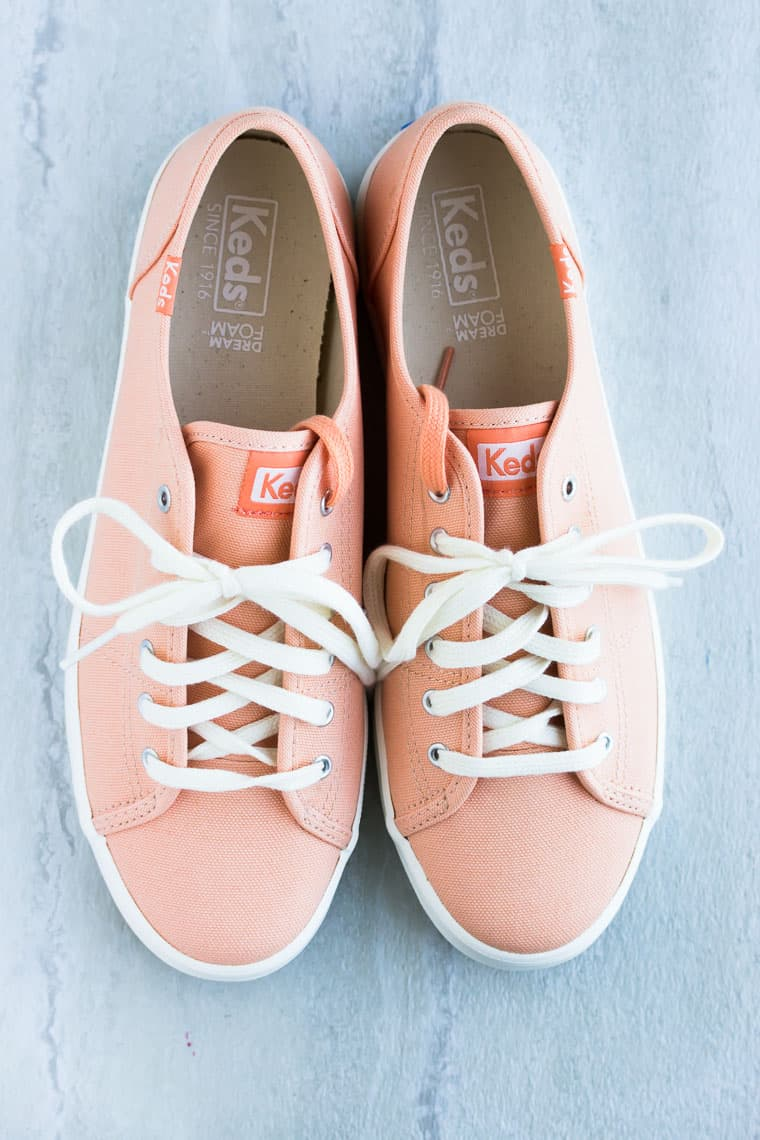 Coral pink sneakers on a white background