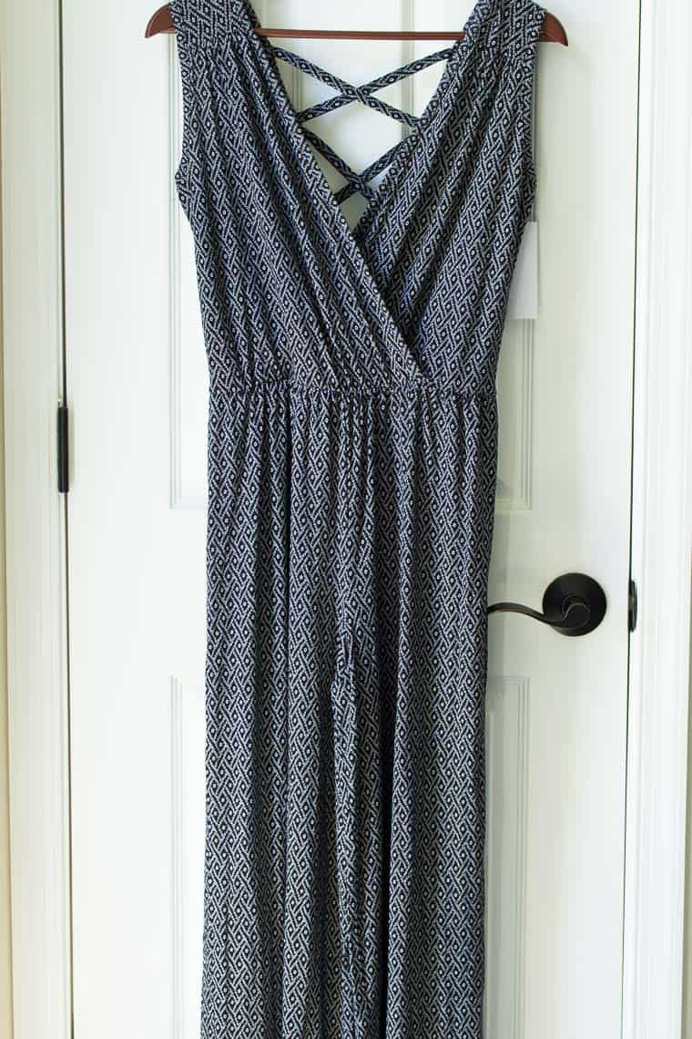 Black and white jumpsuit on a hanger in front of a white door