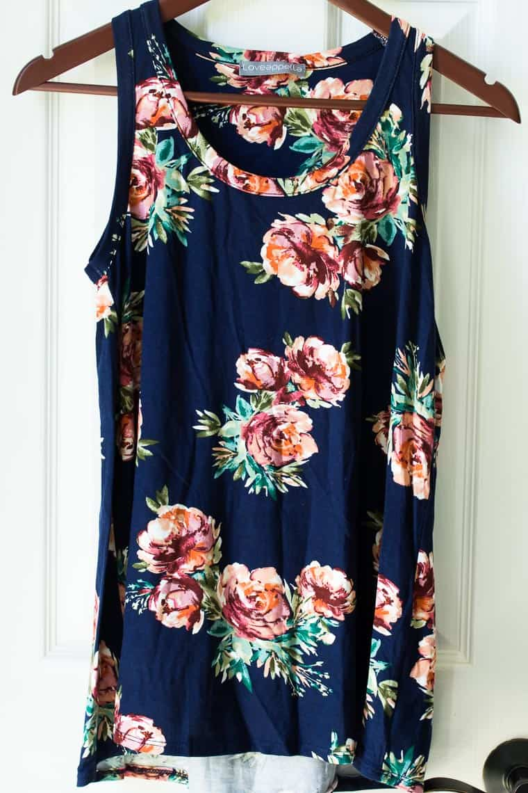 blue shirt with pink flowers on a hanger in front of a white door