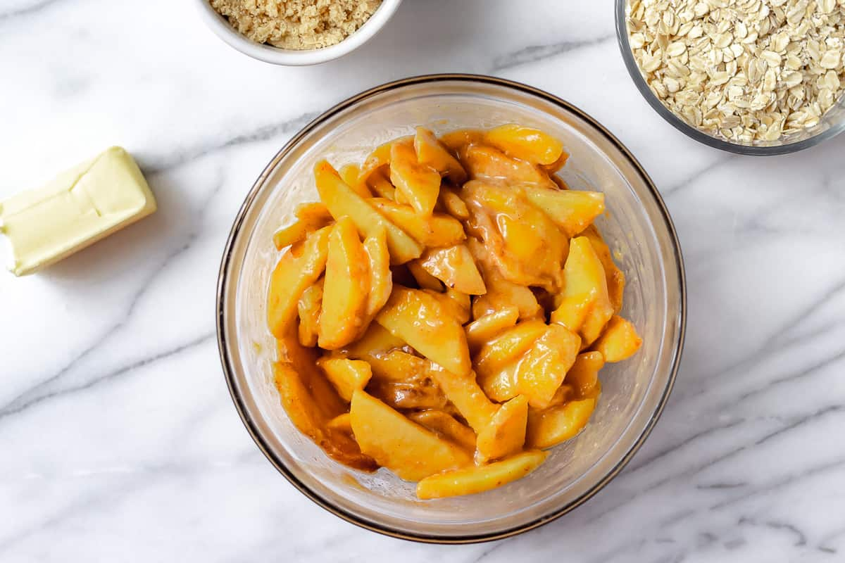 Sliced of peaches with brown sugar, cinnamon and flour in a glass bowl on a marble background with other ingredients around it