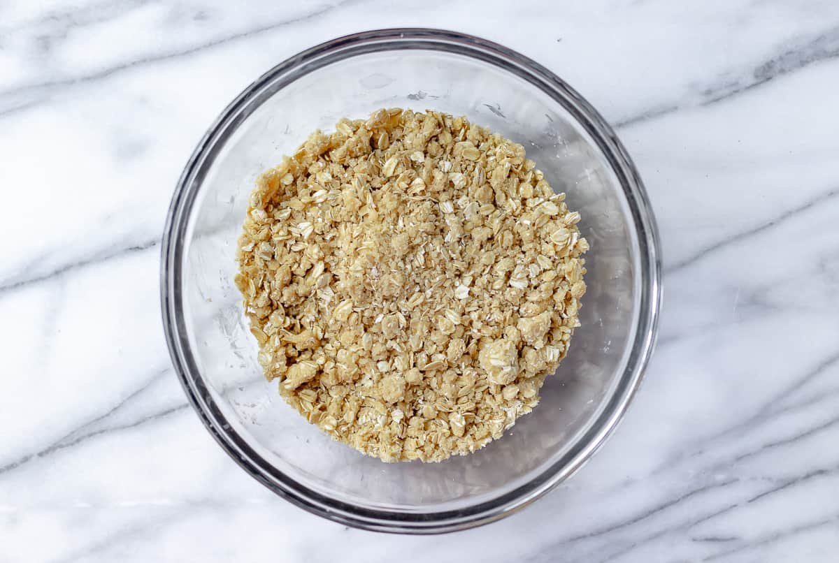 Oat crumble in a glass bowl on a marble background
