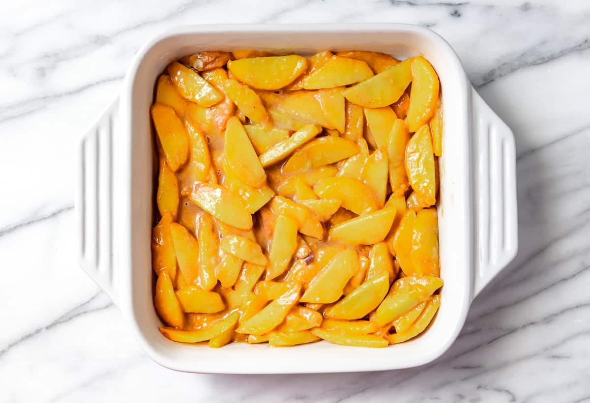 Peached in a white, square baking dish on a marble background