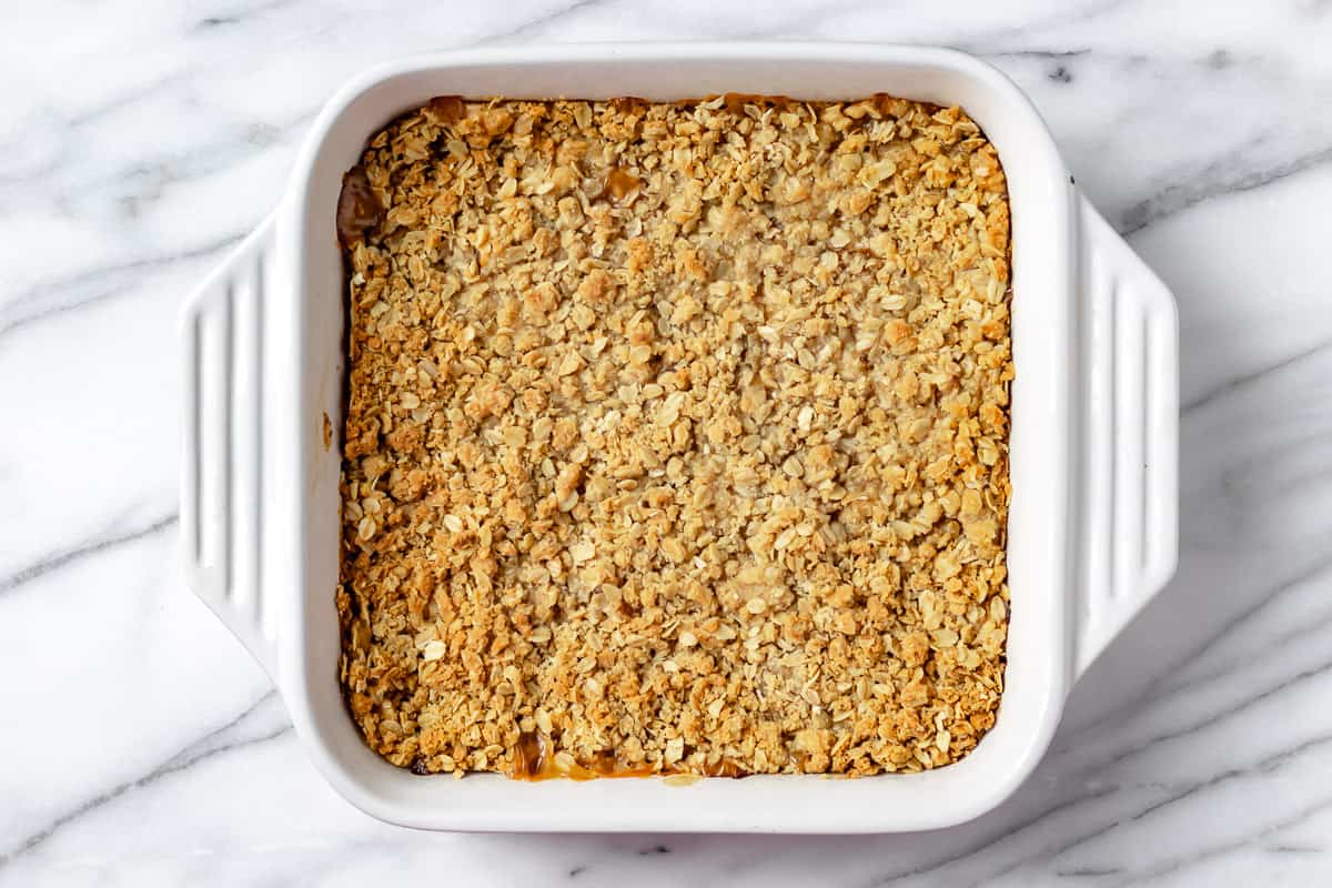 Baked peach crisp in a white, square baking dish on a marble background