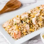 Shrimp quinoa salad on a rectangular serving dish with a wood spoon in the background