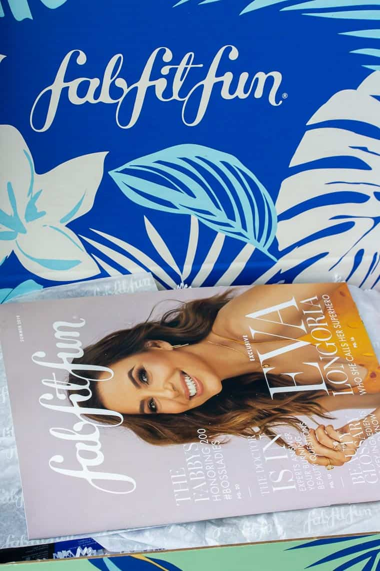 Summer 2019 FabFitFun box open to show blue interior with the logo and the quarterly magazine on top of white packaging