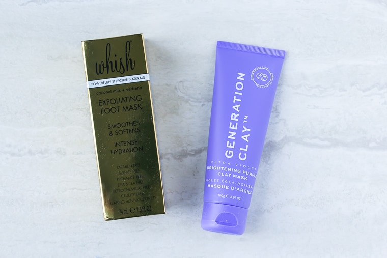 Generation Clay Ultra Violet Brightening Purple Clay Mask next to Whish Exfoliating Foot Mask gold package on a white background