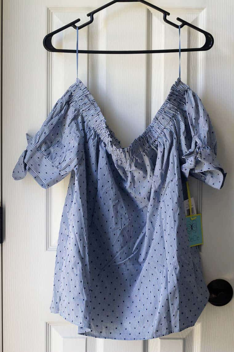 Stitch Fix CECE SPORTSWEAR Raelyn Off the Shoulder Top on a hanger in front of a white door