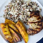 Grilled Cuban Pork Chops, plantains, and rice on a white plate with a dark blue napkin and fork
