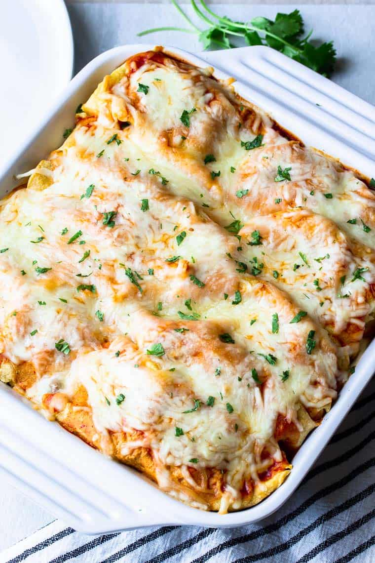 Baked beef and mushroom enchiladas in a white casserole dish on a black and white towels with extra cilantro in the background