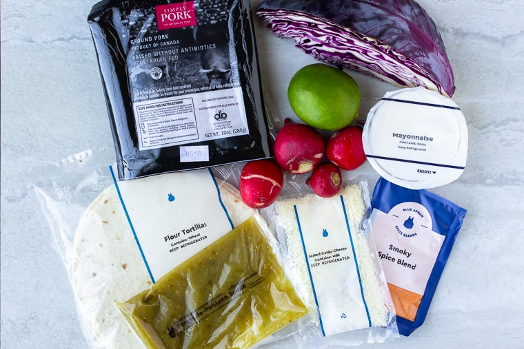 Ingredients for Blue Apron Tomatillo Pork Tacos with Cotija and Cabbage Slaw on a white background