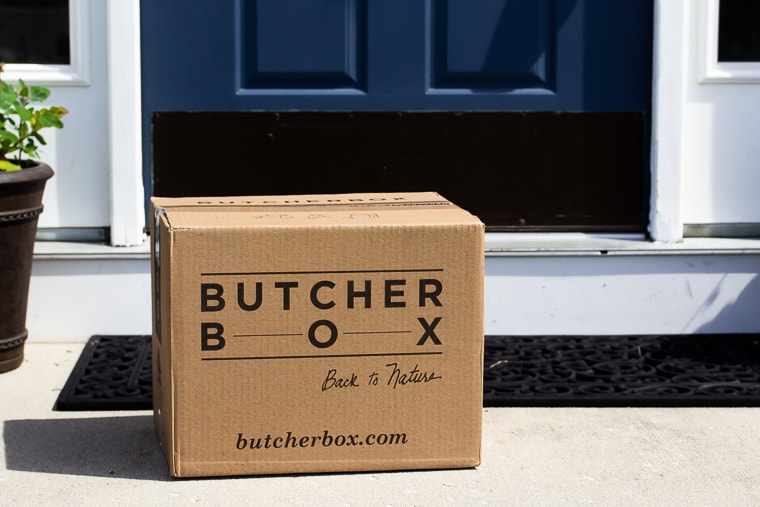 July 2019 Butcher Box sitting on a front porch with a blue door in the background