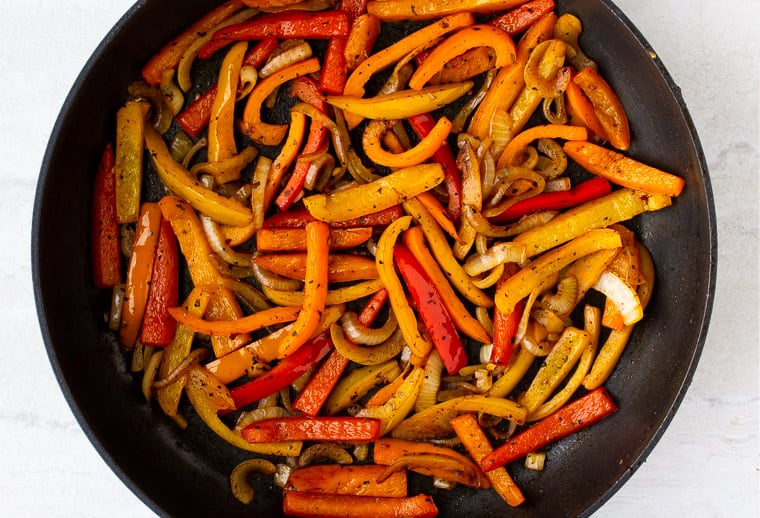 Peppers and onions cooking in a black skillet over a white background