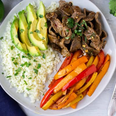beef fajitas with cauliflower rice, peppers, and avocado on a white plate with a blue napkin, limes, and cilantro around it