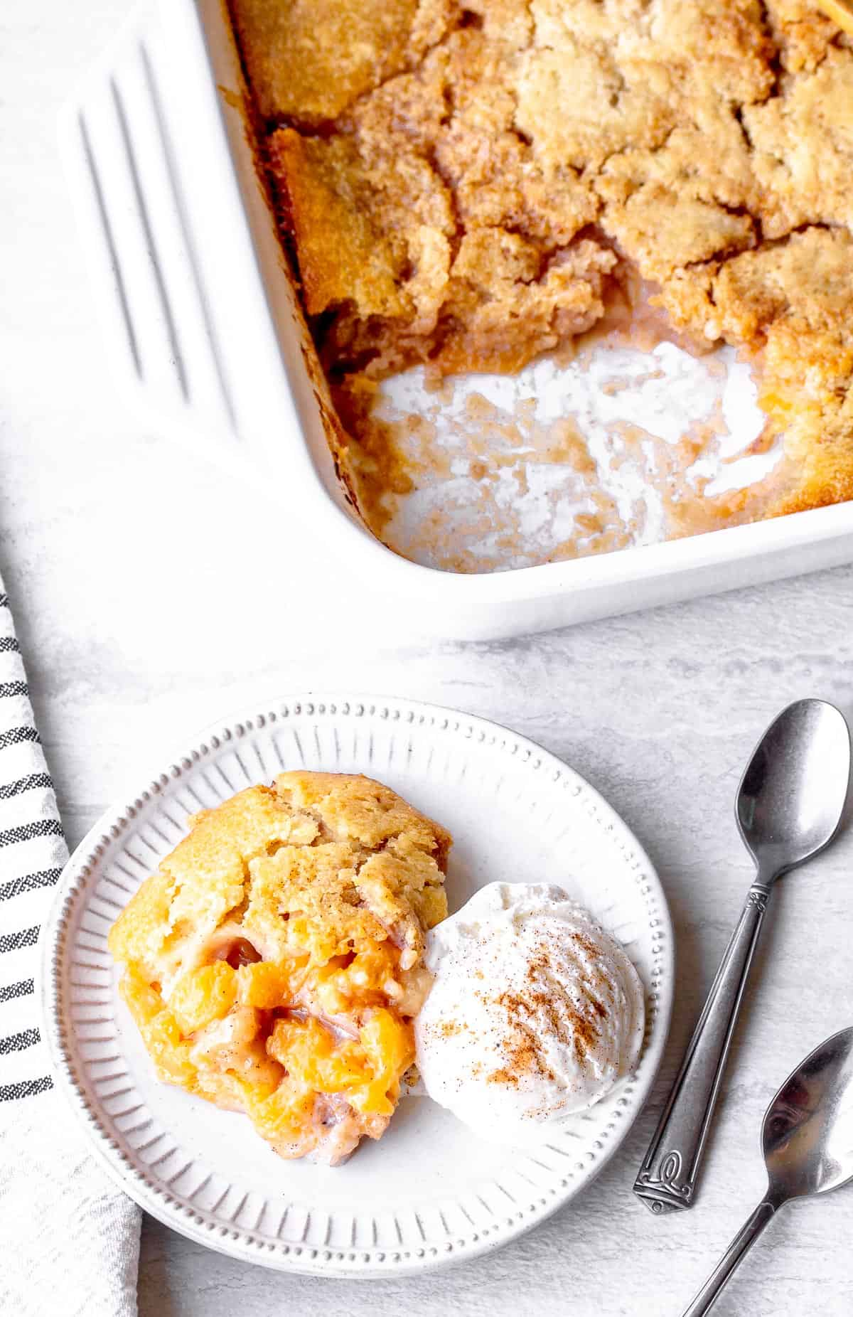 A serving of peach cobbler and vanilla ice cream on a white plate with spoons, a towel and a baking dish in the background