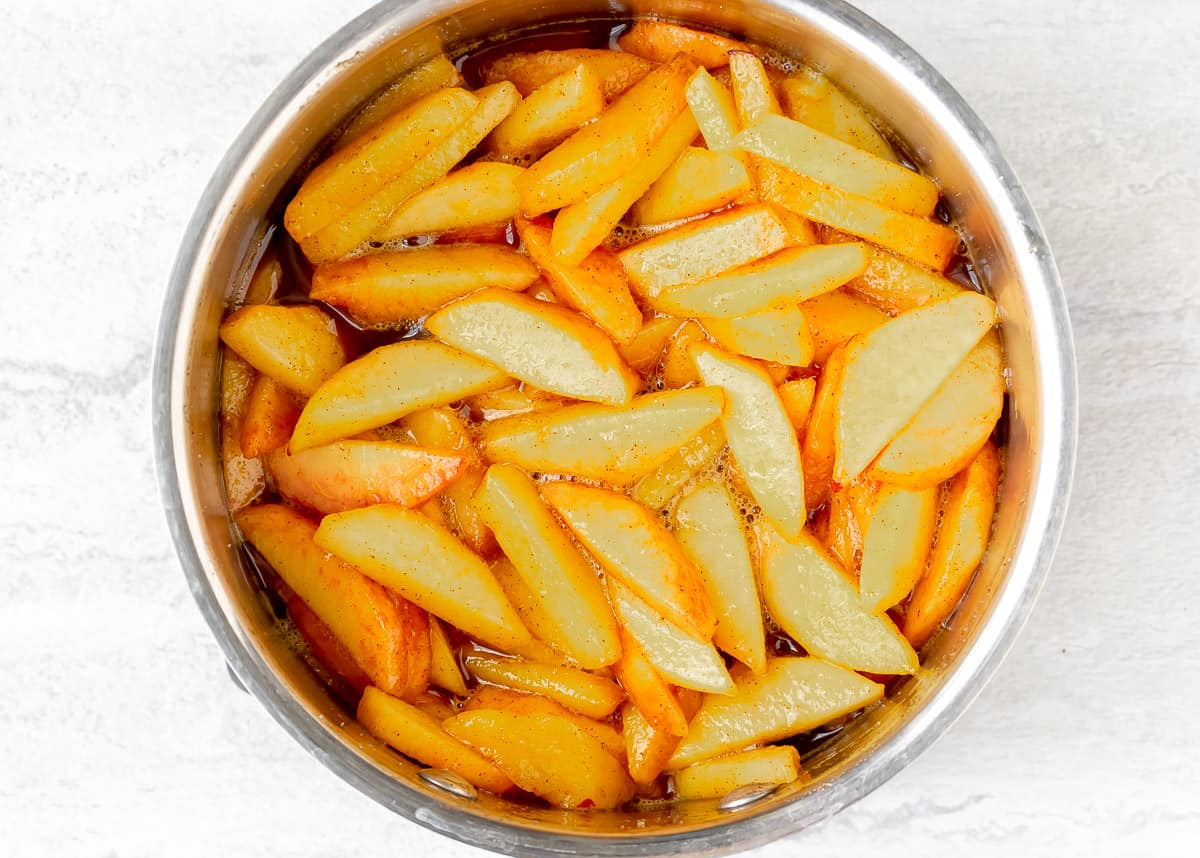 Sliced peaches, brown sugar and cinnamon in a pot over a white background