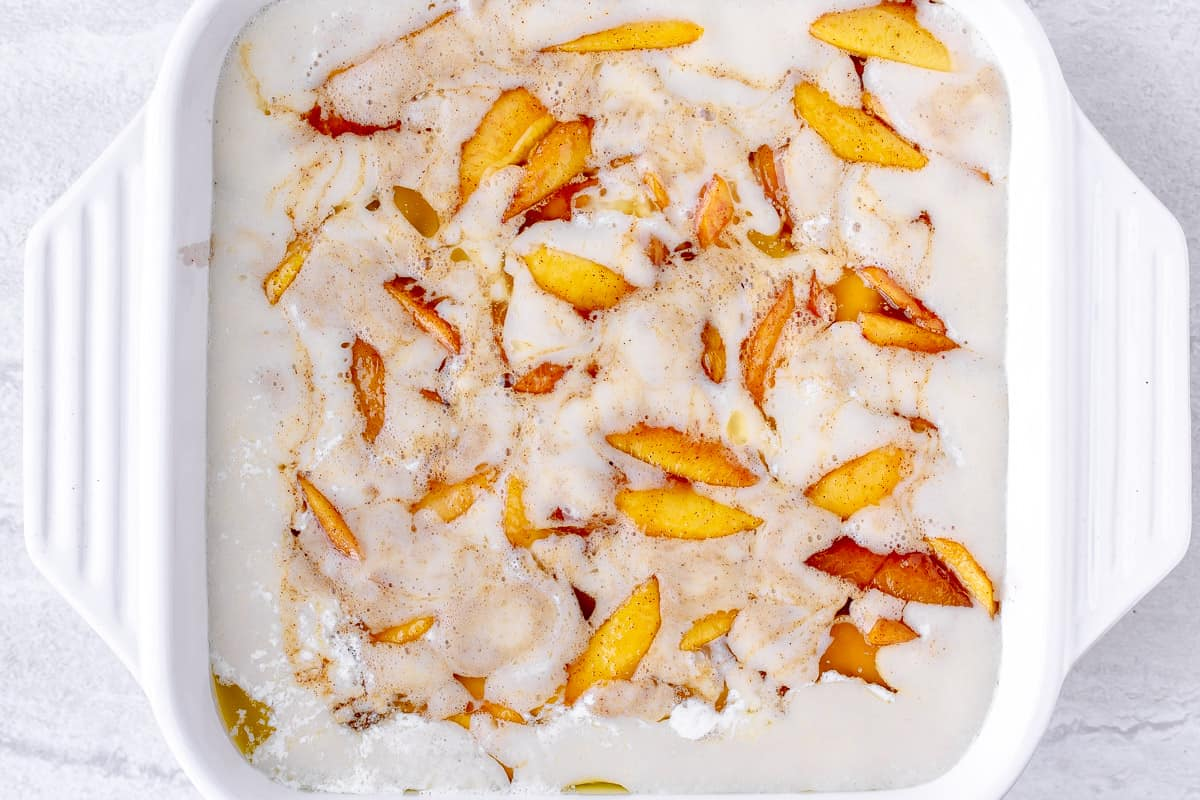 peaches in batter in a white, square baking dish