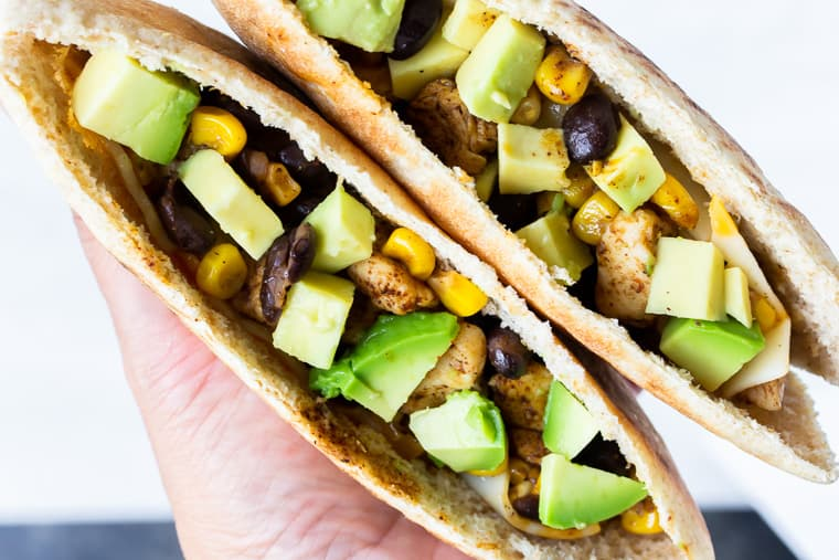 Close up of 2 pita pockets filled with chicken, corn, black beans., cheese, and avocado