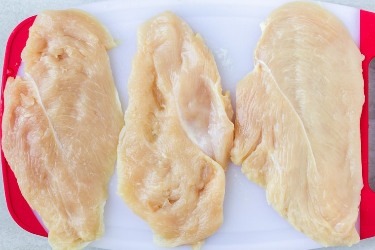 3 thin cut chicken breasts on a white cutting board