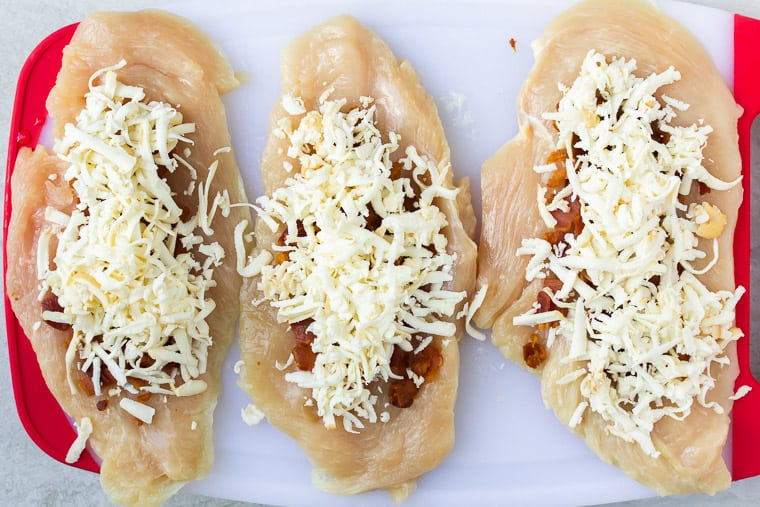 3 thin cut chicken breasts topped with shredded mozzarella and bacon on a white cutting board