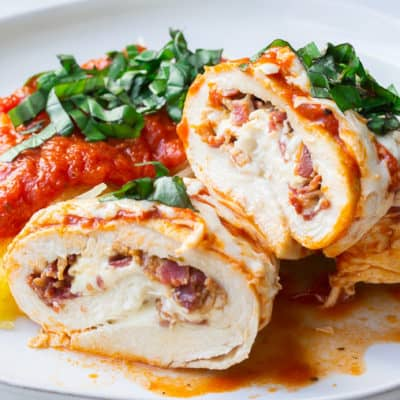 Chicken Roll Ups cut open and stuffed with mozzarella and bacon on a white plate with spaghetti squash