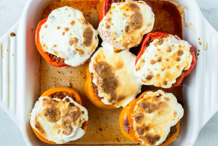 6 baked stuffed peppers with browned, melted mozzarella cheese on top in a white baking dish