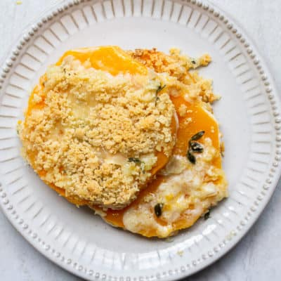 A serving of Butternut Squash Gratin on a small white plate over a white background