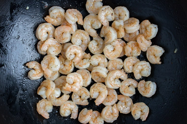 Cooked shrimp in a black skillet