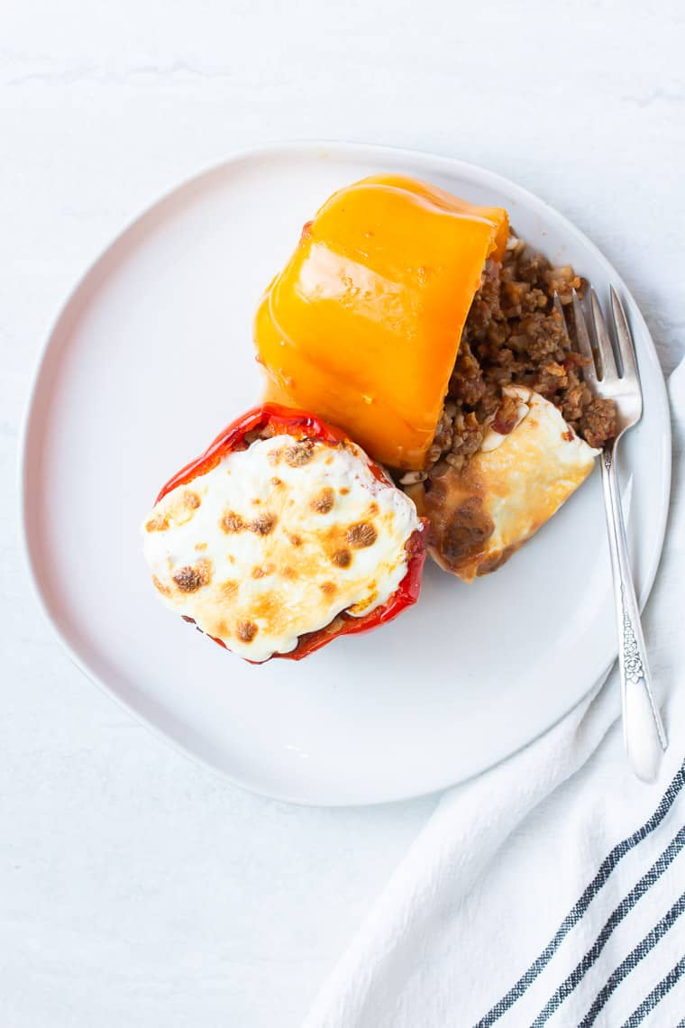 2 keto stuffed peppers on a white plate with a fork and black and white striped napkin on a white background