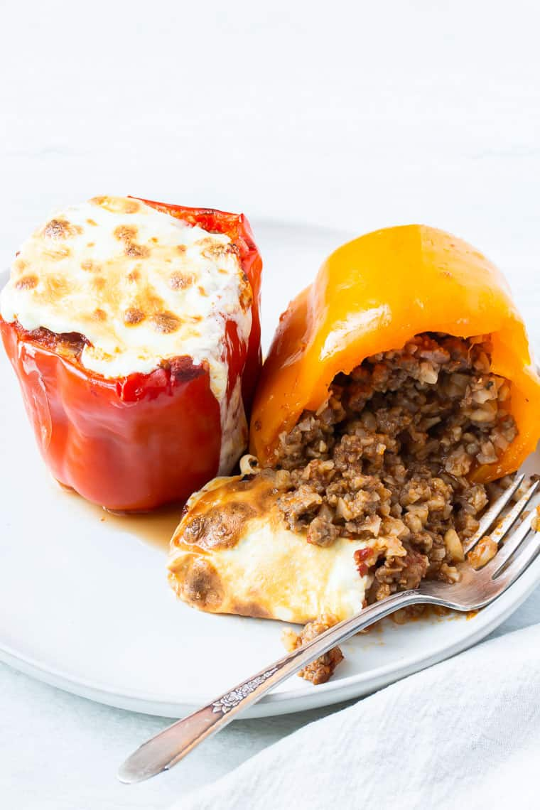 2 Keto Stuffed Peppers on a whit plate with a fork over white background