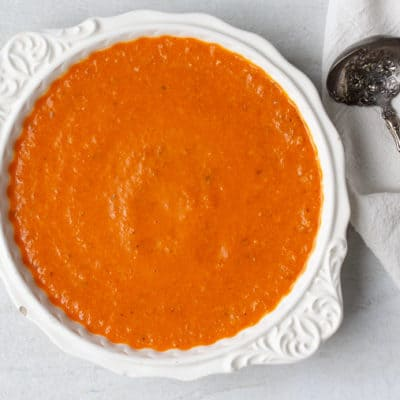 Romesco Sauce in a white bowl over a white background with a metal spoon and black and white towel