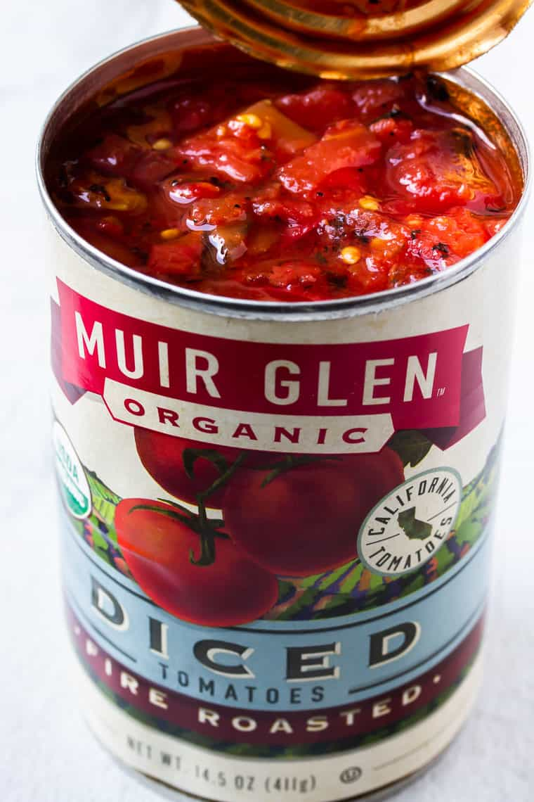 An open can of Muir Glen fire Roasted Diced tomatoes on a white background