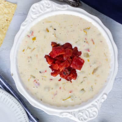 A white bowl of Queso Dip with chips, a spoon, a blue napkin, and a white and blue strip napkin in the background on a white backdrop