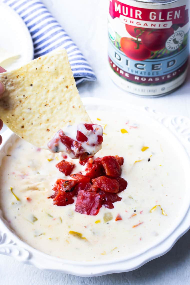 White Queso Dip with a chip taking out a scoop and a can of Muir Glen Fire Roasted Diced Tomatoes, a blue and white napkin, and white plate with chips in the background
